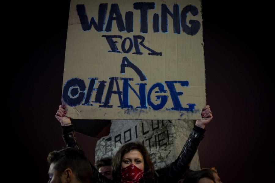 """O tânără ține un banner cu mesajul """"Waiting for a change"""", în Piața Universității, București"""