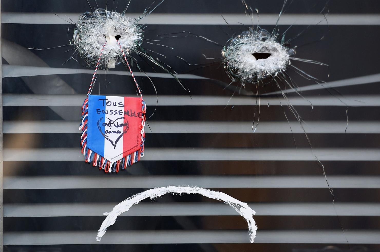 Un fanion în culorile Franței într-un geam găurit de un glonț