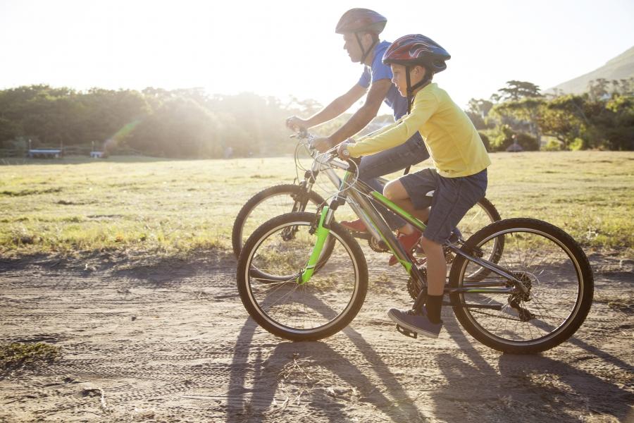 Un tată și fiul său, mergând pe bicicletă