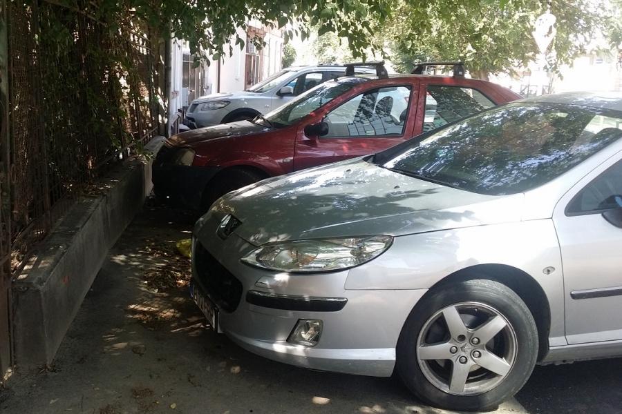 Mașini parcate pe trotuar pe o stradă din București