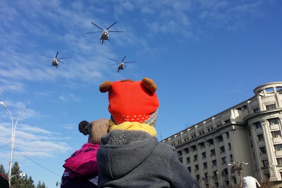 Copiii urmăresc parada militară de 1 Decembrie, în Piața Constituției