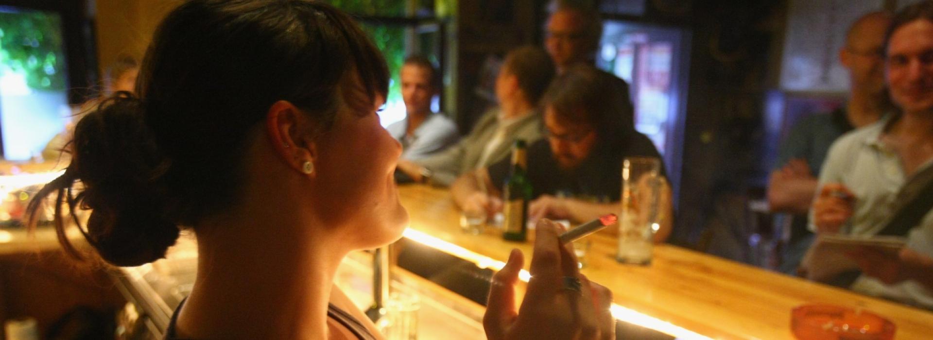 O femeie fumează într-un pub