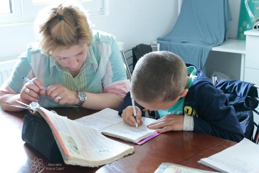 """O voluntară face temele cu un băiat, la asociația """"Ana și Copiii"""""""