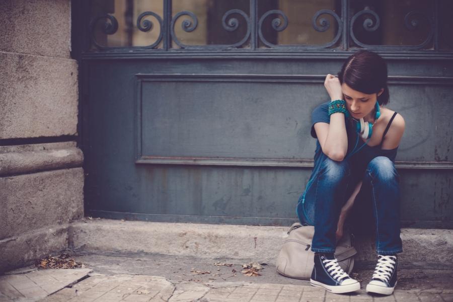 Elevă tristă în fața școlii