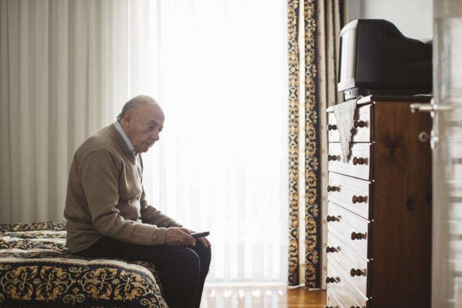 Bătrân în fața televizorului