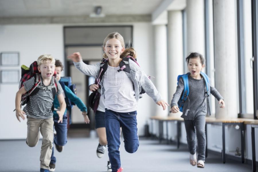 Copii alergând la școală