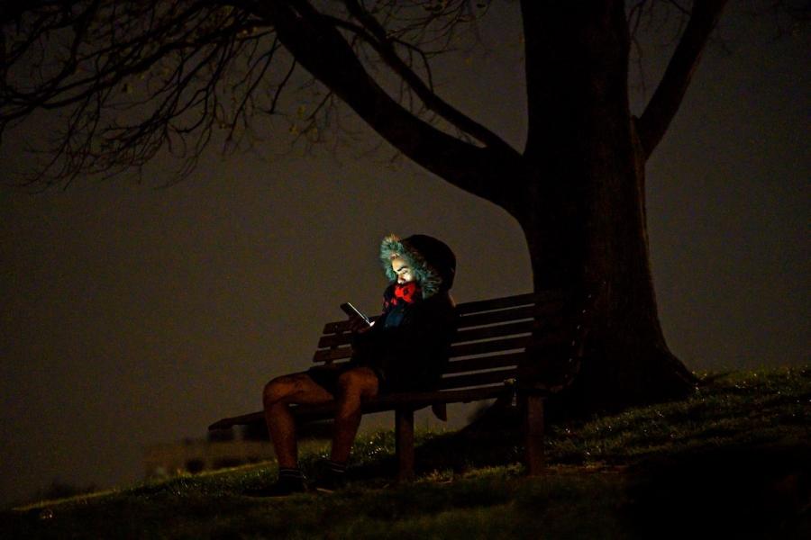 Tănăr pe o bancă în parc seara