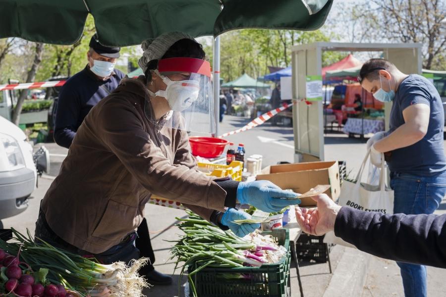 Vânzătoare în piață cu vizieră și mască de protecție