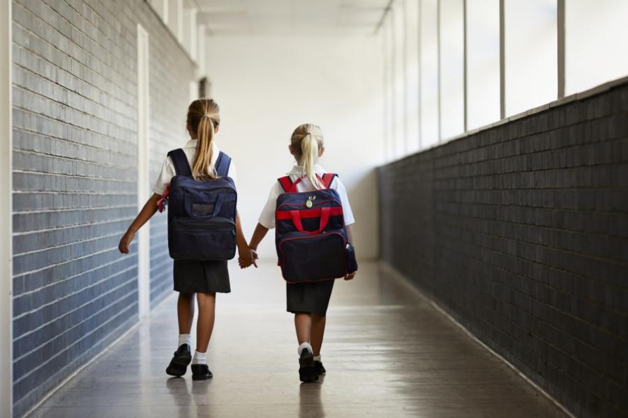 Fetițe ținându-se de mână în drum spre școală